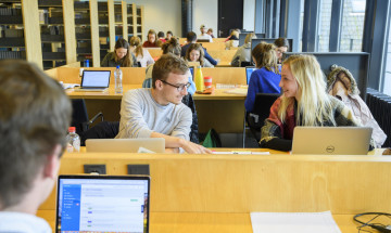 Studenten in de bibliotheek achter computers